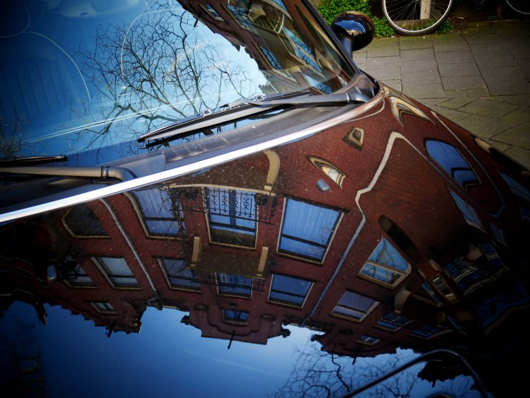 Reflection of Amsterdam houses and blue sky on a car hood - the Netherlands
