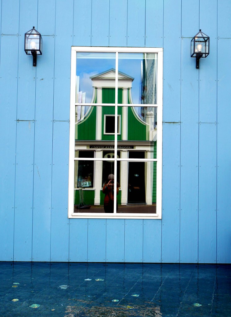 Reflection of a green dutch house on a window of a wooden blue house in Zandaam - the Netherland