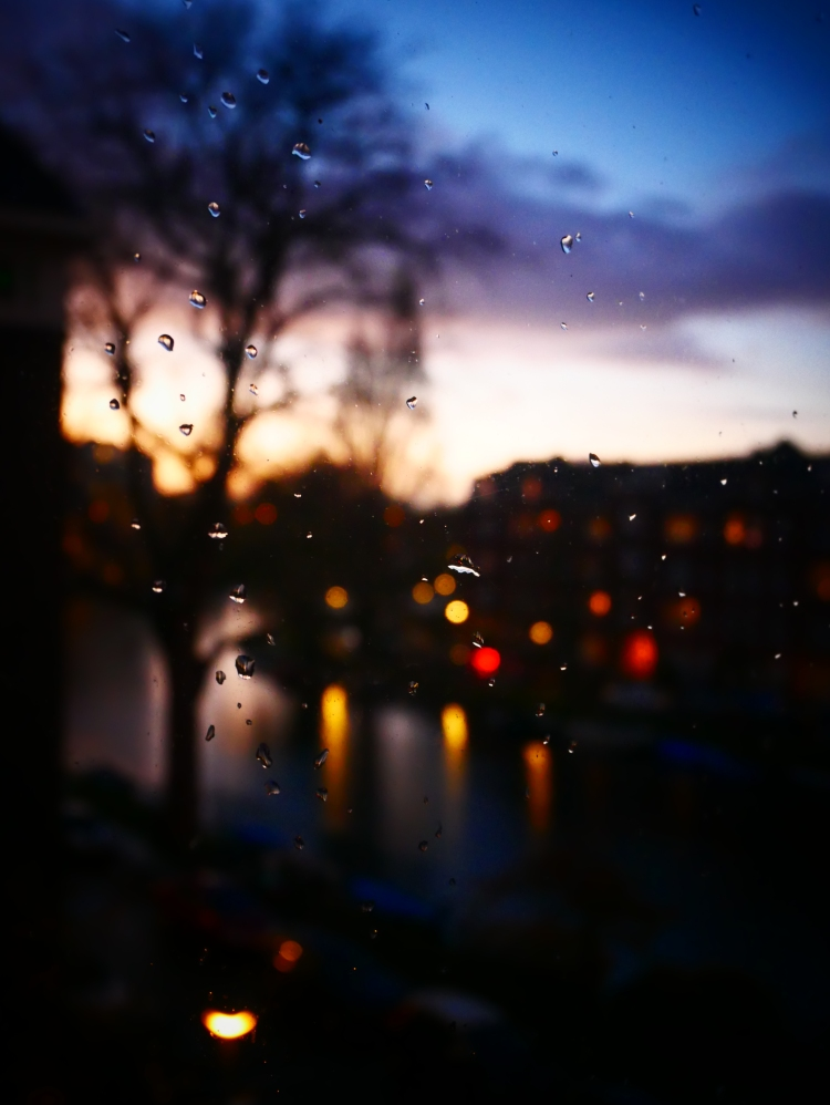Canal view through a window with raindrops at nightfall, with a bokeh background in Amsterdam - the Netherlands