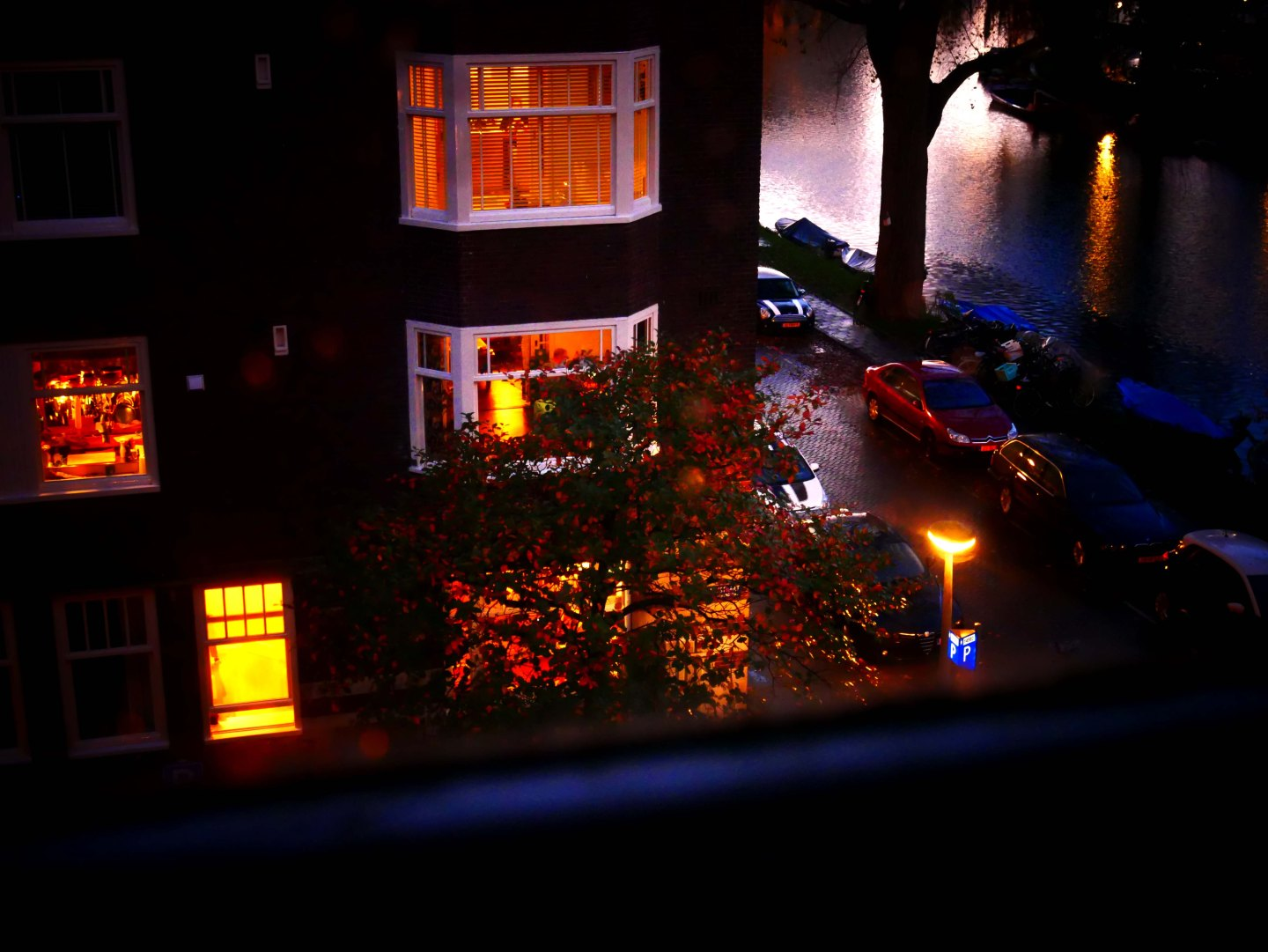 Window view on a quiet neighborhood and on an Amsterdam canal at nightfall - the Netherlands