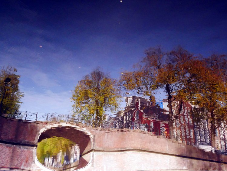 Reflection of a bridge, trees, dutch houses and blue sky on a canal in Amsterdam - the Netherlands. The picture is upside down