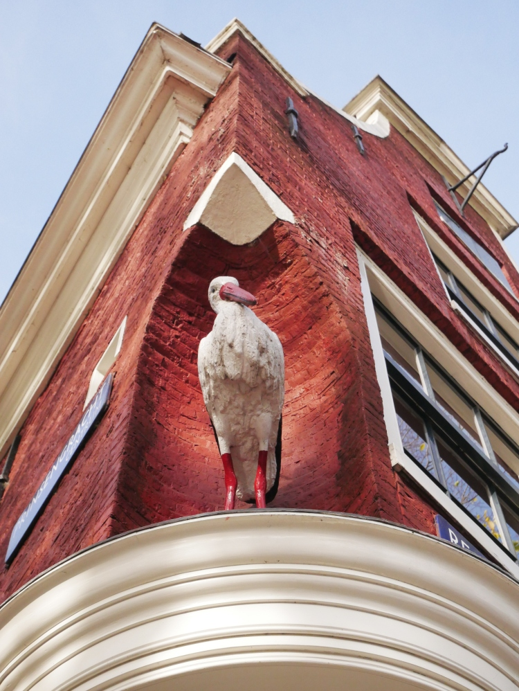 Bottom view of a red Amsterdam house, a stork is carved in the corner