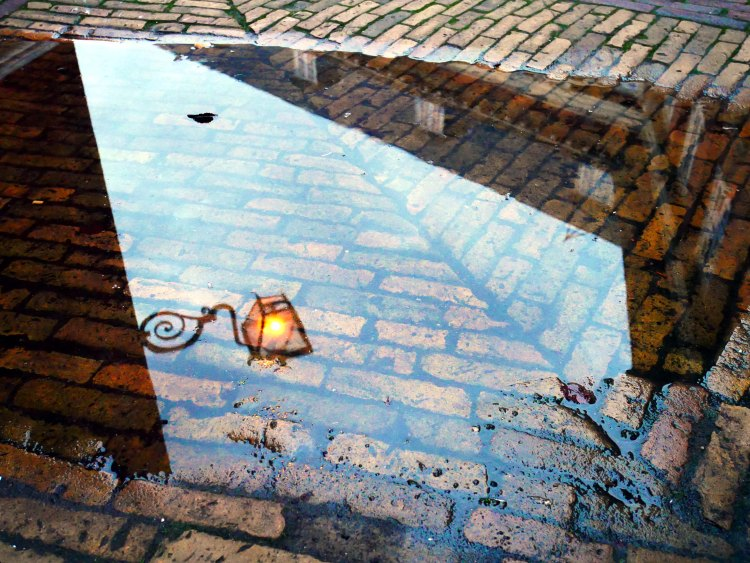 Reflection of a lit street lamp on a rain puddle in Amsterdam - the Netherlands