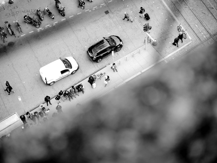 View from a top of a building of cars waiting at the traffic light and pedestrians walking or waiting for the bus in Bordeaux - France