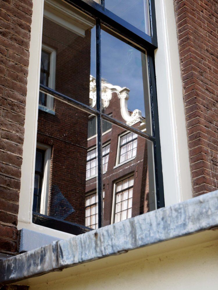 Reflection of Amsterdam houses and blue sky on a window - the Netherlands