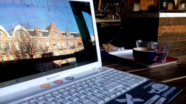 Reflection of Amsterdam houses and blue sky on a laptop screen in a cafe - the Netherlands