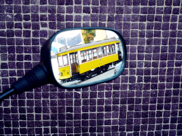 Reflection of a yellow tram on a scooter mirror with a purple mosaïc wall in the background in Coïmbra - Portugal