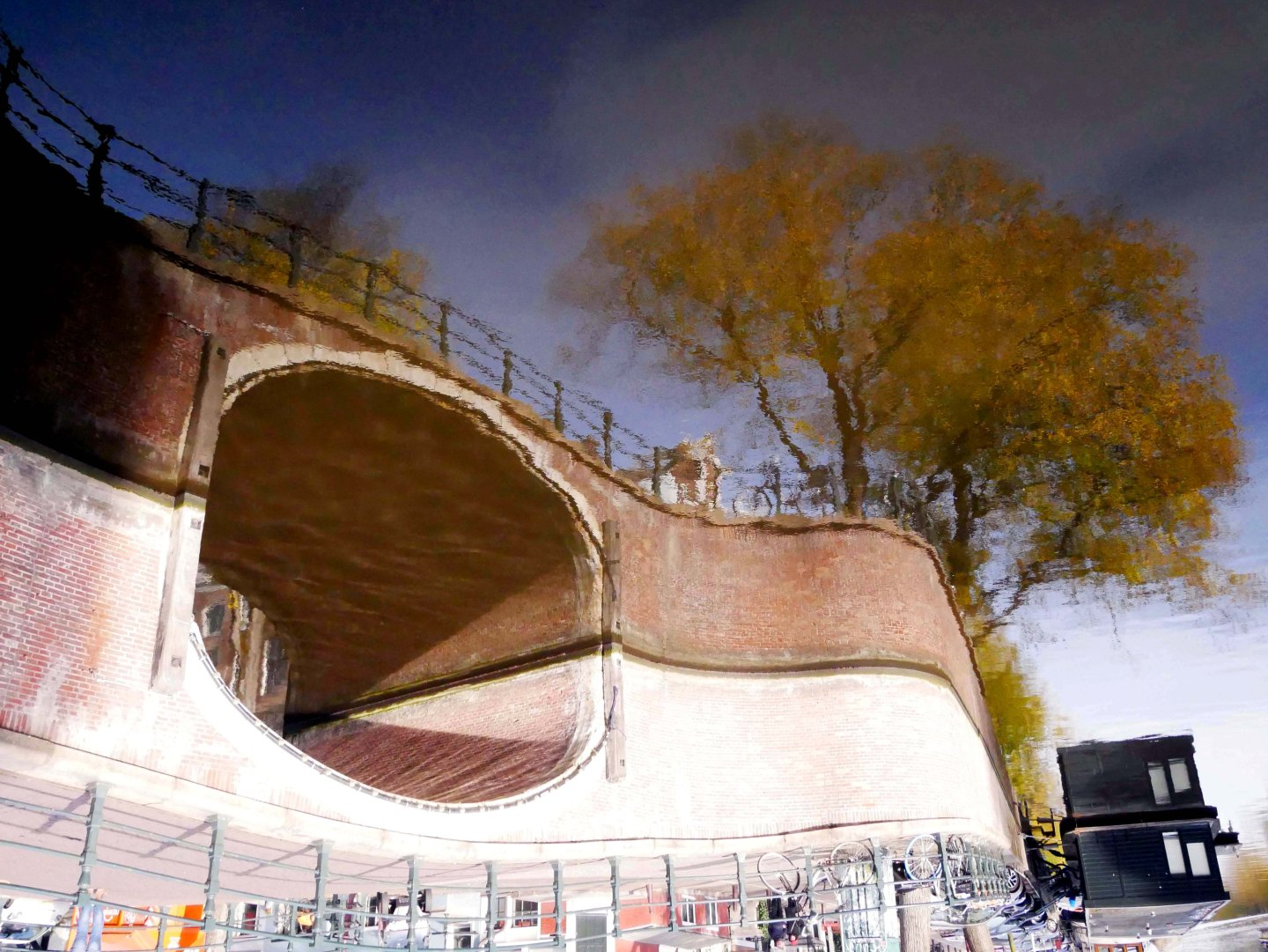 Reflection of a bridge, trees, houseboat, bikes and blue sky on a canal in Amsterdam - the Netherlands. The picture is upside down