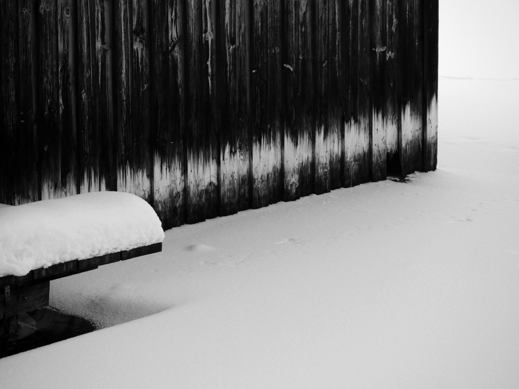 Wall of a dark wooden cabin in contrast with the white snowy ground in Germany - Spitzingsee. By its side, a bench covered with snow.