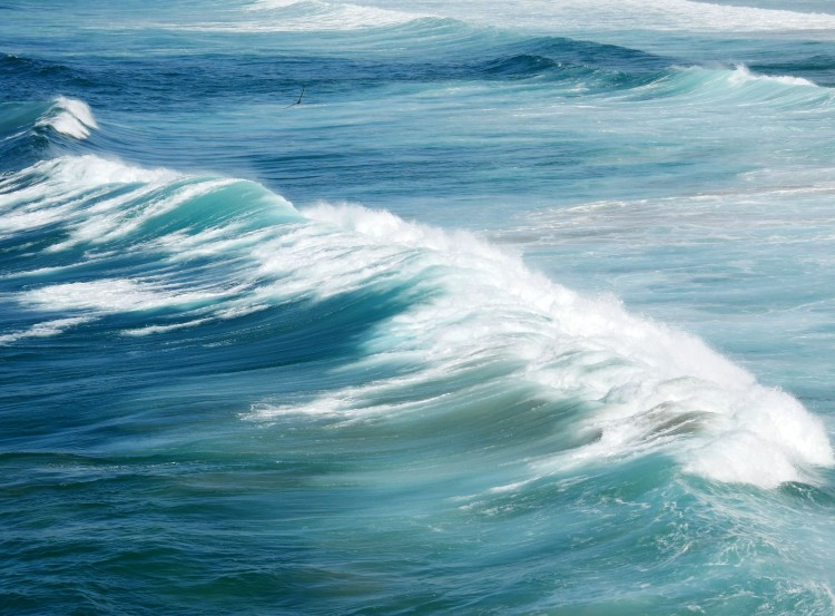 Waves breaking on the shore, showing several shades of blue of the ocean