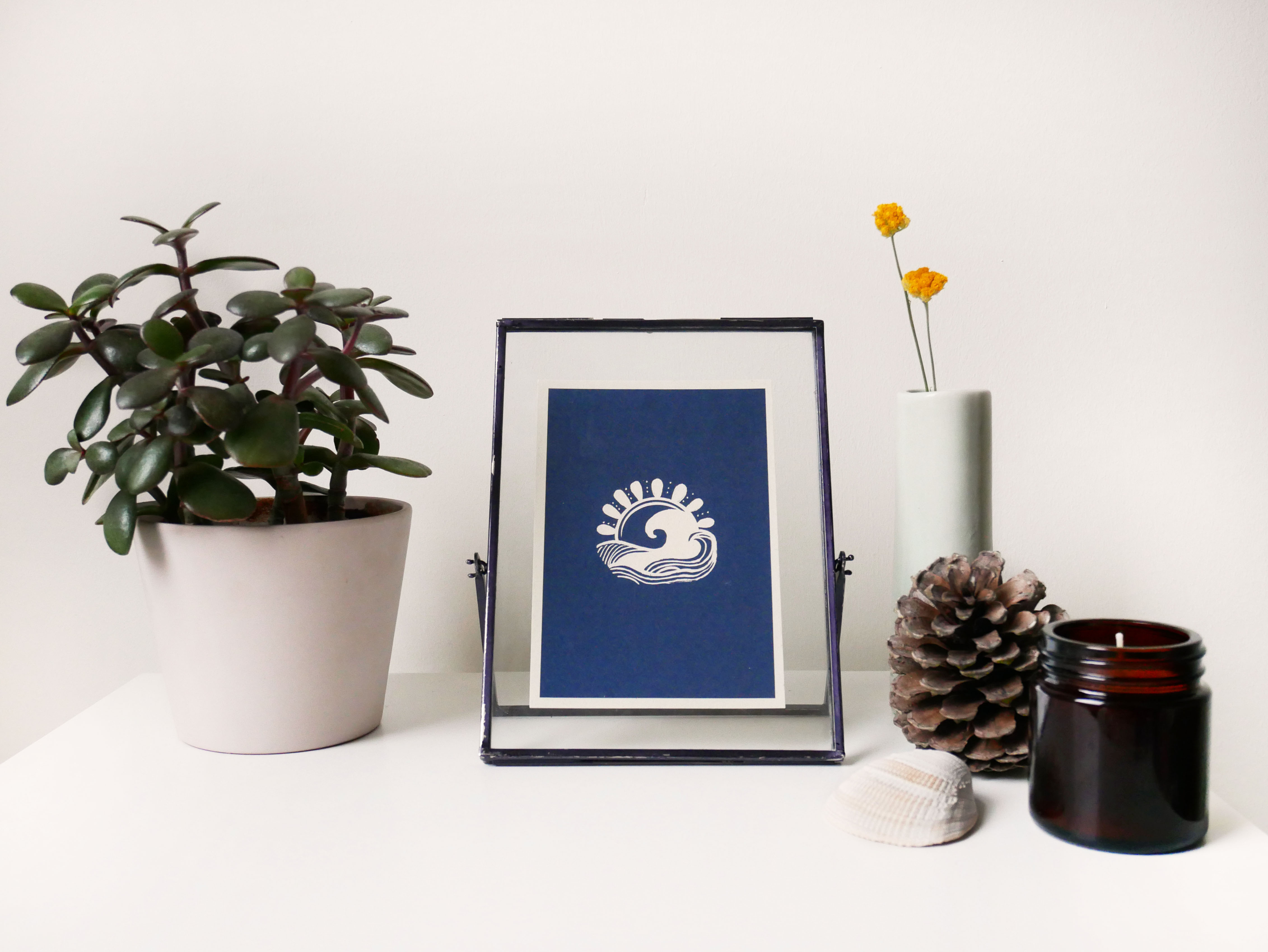 Decorative illustration in a black frame next to a green plant, candle, shell, pine cone and decorative vase