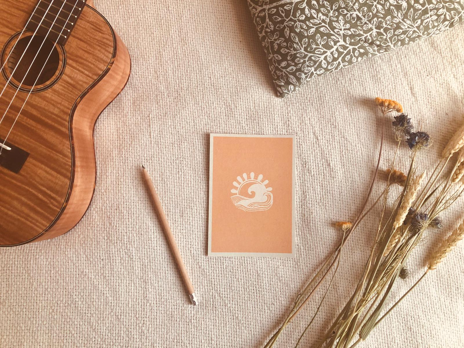 Orange and white postcard on a white blanket next to a pencil, ukulele, dried flowers, cushion