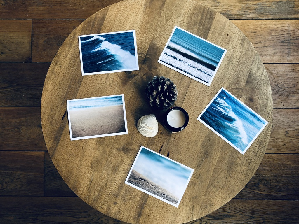 Five ocean photography postcards on a wooden table
