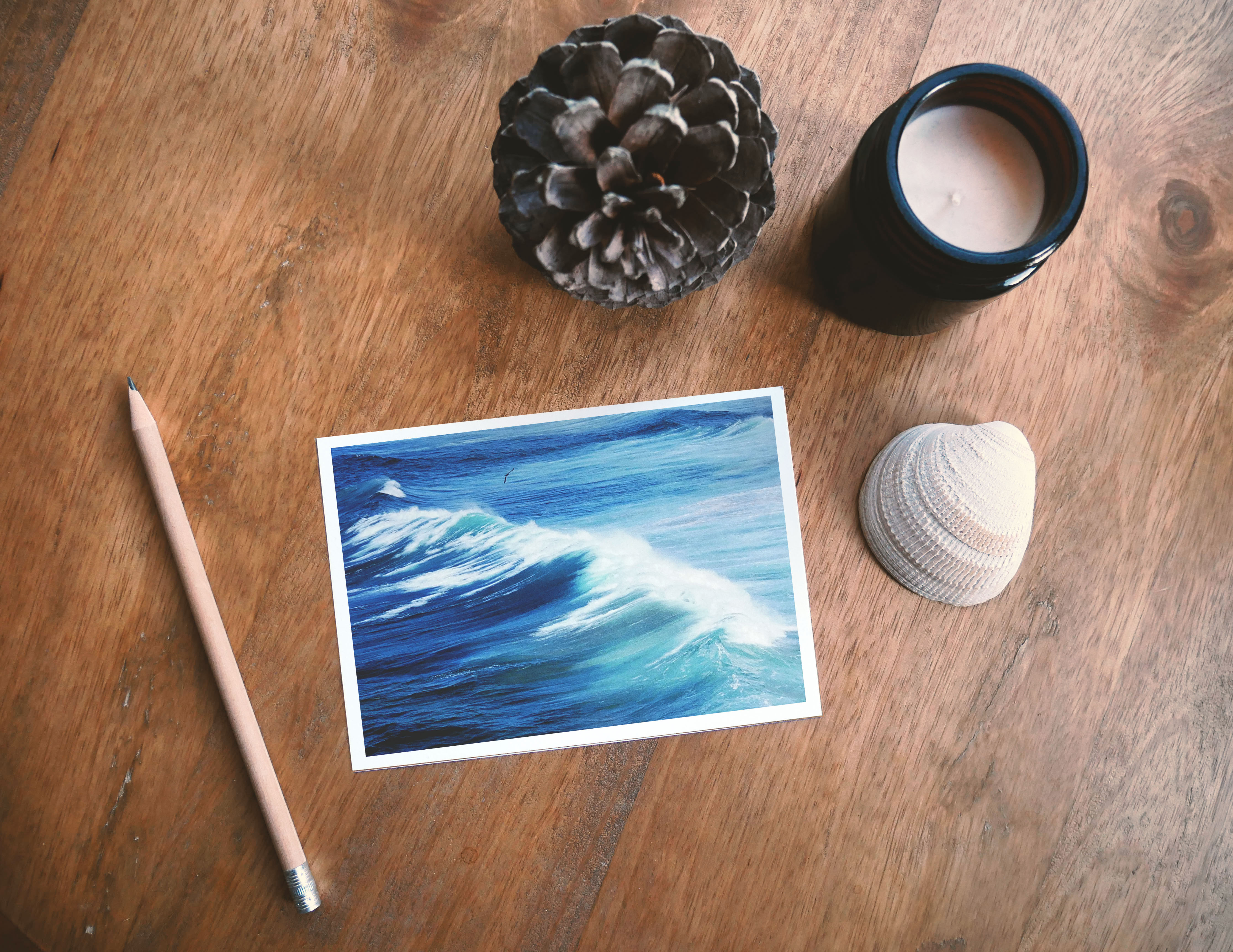Ocean postcard on a wooden table next to a pencil, a shell, a candle and a pine cone