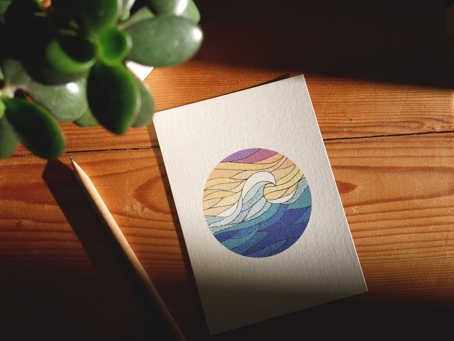 Colorful postcard on a wooden table near a pen and a plant
